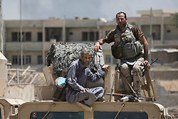 © Licensed to London News Pictures. 15/06/2017. Mosul, Iraq. An elderly Mosul resident sits on the roof of an Iraqi Army Humvee after being ferried to safety across open ground watched by Islamic State snipers.<br /> <br /> Despite heavy fighting between the Islamic State and Iraqi Security Forces many civilians have started to leave ISIS territory in West Mosul. Mosul residents, many of whom have been in hiding in their homes since the start of the West Mosul Offensive, often have to run through ISIS sniper and machine gun fire to reach the safety of Iraqi Security Forces positions. Photo credit: Matt Cetti-Roberts/LNP