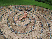 Outdoor overhead view of a nude woman reclining in the middle of a pebble and stone spiral maze