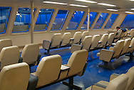 a lone ferry commuter sits in a ferry lounge on a Washington state DOT ferry on Puget Sound in Washington state, USA