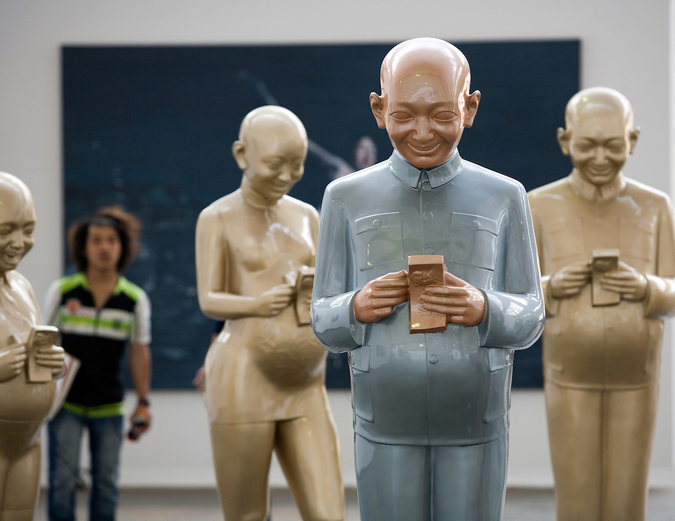 Visitors looka at a collection os sculptures depicitng people counting money, on display at a gallery in Beijing's trendy Dashanzi Art District May 4, 2007.