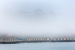 © Licensed to London News Pictures. 01/10/2015. Whitby, UK. Picture shows the coloured beach huts in Whitby covered in fog. The fishing town of Whitby awoke to a thick covering of fog but the weather is due to brighten up later today. Photo credit: Andrew McCaren/LNP