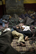 Two young homeless friends lie together in the Fatepuri night shelter for the homeless in Old Delhi, India.