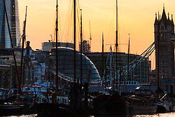 London, March 10th 2015. The sun sets over London after a warm early spring day. PICTURED: The masts of Dutch sailing barges with City Hall and Tower Bridge as a backdrop.