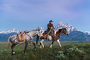 Wrangler and his horse pass in front of the Alpenglow light and the jagged peaks of the Grand Teton mountain range in Jackson Hole, WY.
