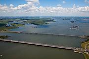 Nederland, Zuid-Holland, Hollandsch Diep, 12-06-2009; Hollandsch Diep met de Moerdijkbruggen: onder de brug voor het autoverkeer (A16), in het midden de nieuwe brug voor de HSL ontworpen door Benthem Crouwel en daar direct de spoorbrug voor gewonen reinen. In de achtergrond: links de Dordtsche Biesbosch, midden de monding van de Nieuwe Merwede, geheel rechts de rivier de Amer (overgaand in Bergsche Maas). Rechts naar de horizon,  Nationaal Park De Biesbosch..The Moerdijk bridges, in the middle the new railway bridge for the TGV (HST), the bridge is located next to the existing rail bridge..Swart collectie, luchtfoto (25 procent toeslag); Swart Collection, aerial photo (additional fee required).foto Siebe Swart / photo Siebe Swart