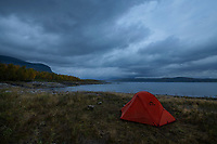 Tent wild camping beneath heavy clouds on the shore of lake Riebnes, Kungsleden Trail, Lapland, Sweden