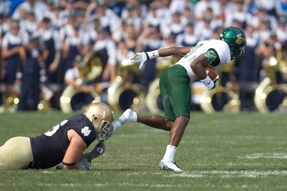 South Florida wide receiver Terrence Mitchell (#10) loses his shoe on the tackle attempt of Notre Dame offensive guard Andrew Nuss (#76) in action during NCAA football game between Notre Dame and South Florida.  The South Florida Bulls lead the Notre Dame Fighting Irish 16-0 at halftime in game at Notre Dame Stadium in South Bend, Indiana.  The game has been delayed due to rain storms and lightning in the area.