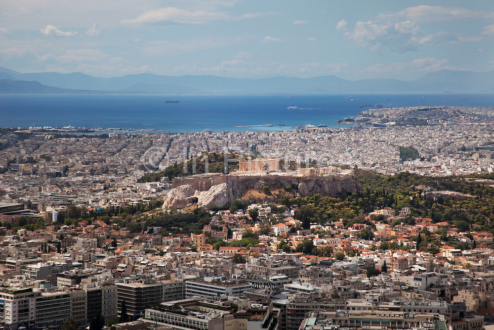 View across the sprawling city of Athens from the summit of Lykavittos Hill in the North Eastern section of the centre of the city. In this direction you can see the Parthenon sitting firmly atop the Acropolis. The spectacular views can be seen in all directions from this vantage point, giving aerial and panoramic views of the vast urban spread of buildings and humanity below. Athens is the capital and largest city of Greece. It dominates the Attica periphery and is one of the world's oldest cities, as its recorded history spans around 3,400 years. Classical Athens was a powerful city-state. A centre for the arts, learning and philosophy.