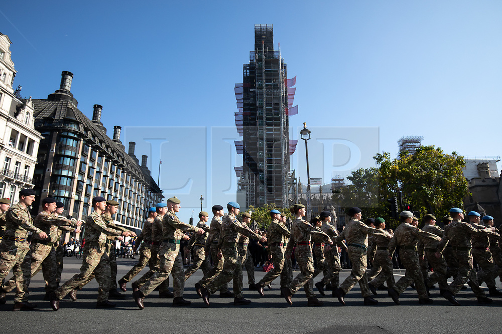 """© Licensed to London News Pictures. 10/10/2018. London, UK. 120 army personnel march through Parliament Square, led by the Band of the Grenadier Guards, to a """"welcome home"""" reception in the Palace of Westminster, to highlight the breadth of the British Army's current activities. Photo credit : Tom Nicholson/LNP"""