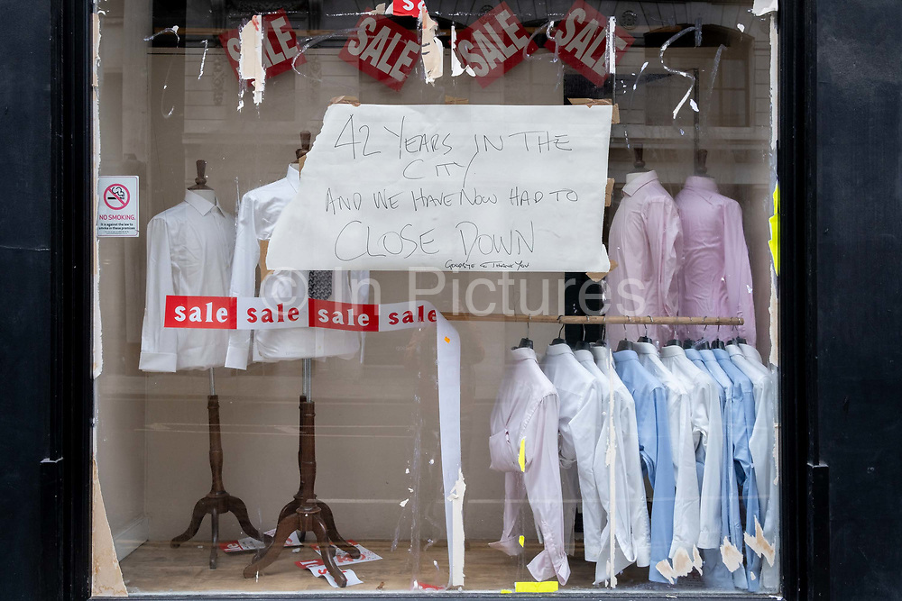 As the UK government tells the nation to prepare for the worst two weeks of the Coronavirus pandemic, a warning aimed at the population to stay at home and minimise contact with others, but in the week when new vaccination centres are opening, is a small menswear shop now forced to close after 42 years in business on Moorgate in the capitals financial district, on 11th January 2021, in the City of London, England.