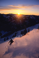 A backountry skier makes turns on the west side of Teton Pass at sunset in Jackson Hole, Wyoming.