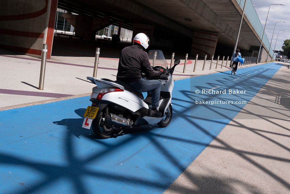 A male moped rider follows a woman cyclist, illegally riding on the dedicated cycle path that travels alongside the A13 Newham Way in Canning Town in the East End, on 11th August 2021, in London, England.