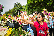 """22 JULY 2013 - PHRA PHUTTHABAT, THAILAND: People put flowers on a truck carrying a statue of the Buddha during the Tak Bat Dok Mai at Wat Phra Phutthabat in Saraburi province of Thailand, Monday, July 22. Wat Phra Phutthabat is famous for the way it marks the beginning of Vassa, the three-month annual retreat observed by Theravada monks and nuns. The temple is highly revered in Thailand because it houses a footstep of the Buddha. On the first day of Vassa (or Buddhist Lent) people come to the temple to """"make merit"""" and present the monks there with dancing lady ginger flowers, which only bloom in the weeks leading up Vassa. They also present monks with candles and wash their feet. During Vassa, monks and nuns remain inside monasteries and temple grounds, devoting their time to intensive meditation and study. Laypeople support the monastic sangha by bringing food, candles and other offerings to temples. Laypeople also often observe Vassa by giving up something, such as smoking or eating meat. For this reason, westerners sometimes call Vassa the """"Buddhist Lent.""""        PHOTO BY JACK KURTZ"""