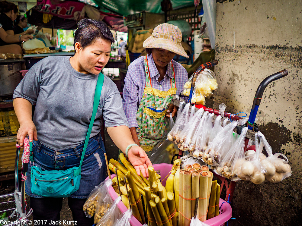 08 JUNE 2017 - BANGKOK, THAILAND: A shopper buys snacks from a vendor who uses a hand truck in Khlong Toey Market, Bangkok's main fresh market. Thai consumer confidence dropped for the first time in six months in May following a pair of bombings in Bangkok, low commodity prices paid to farmers and a sharp rise in the value of the Thai Baht versus the US Dollar and the EU Euro. The Baht is surging because of political uncertainty, related to Donald Trump, in the US and Europe. The Baht's rise is being blamed for a drop in Thai exports. This week the Baht has been trading at around 33.90 Baht to $1US, it's highest point in two years.      PHOTO BY JACK KURTZ
