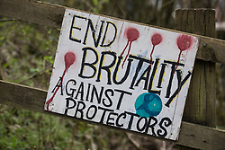 Wendover, UK. 9th April, 2021. A sign reading End Brutality Against Protectors is pictured outside Wendover Active Resistance Camp, which is occupied by activists opposed to the HS2 high-speed rail link. Tree felling work for the project is now taking place at several locations between Great Missenden and Wendover in the Chilterns AONB, including directly opposite the camp.