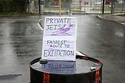 A sign displayed by Extinction Rebellion climate activists on a fuel barrel outside an entrance to Farnborough Airport is pictured on 2nd October 2021 in Farnborough, United Kingdom. Activists blocked three entrances to the private airport to highlight elevated carbon dioxide levels produced by super-rich passengers using private jets and greenwashing by the airport in announcing a switch to sustainable aviation fuel SAF.