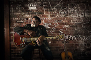 An elderly african-american blues musician poses in a dark bar with unique brick wall with his red electric guitar.