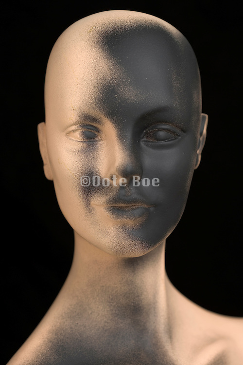 a mannequin's face with a black spray painted face