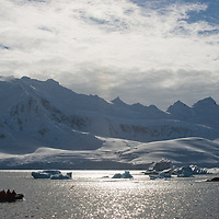 Tourists in a zodiac raft cruise towards icebergs in the Neumayer Channel near the Antarctic Peninsula, Antarctica. Mountains and glaciers on Anvers Island rise in the background.