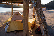 Liana Welty watches the sunset from her tent under a palapa in Playa Santispac, Baja California Sur, Mexico.