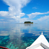A small outrigger canoe steers towards an uninhabited island near Siargao, The Philippines.