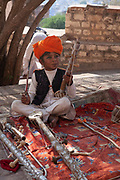A young boy with a musical instrument at the Mehrangarh Jodhpur Fort on 5th November 2009, in Jodhpur, Rajasthan, India. Built in around 1459 by Rao Jodha, it is one of the largest forts in India, it is situated 410 feet 125m above the city and known for the intricate carvings and expansive courtyards within.