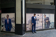 A young businessman checks messages with a cigarette by posters featuring men in matching blue suits in the City of London, the capitals financial district aka The Square Mile, on 29th August 2018, in London, England.