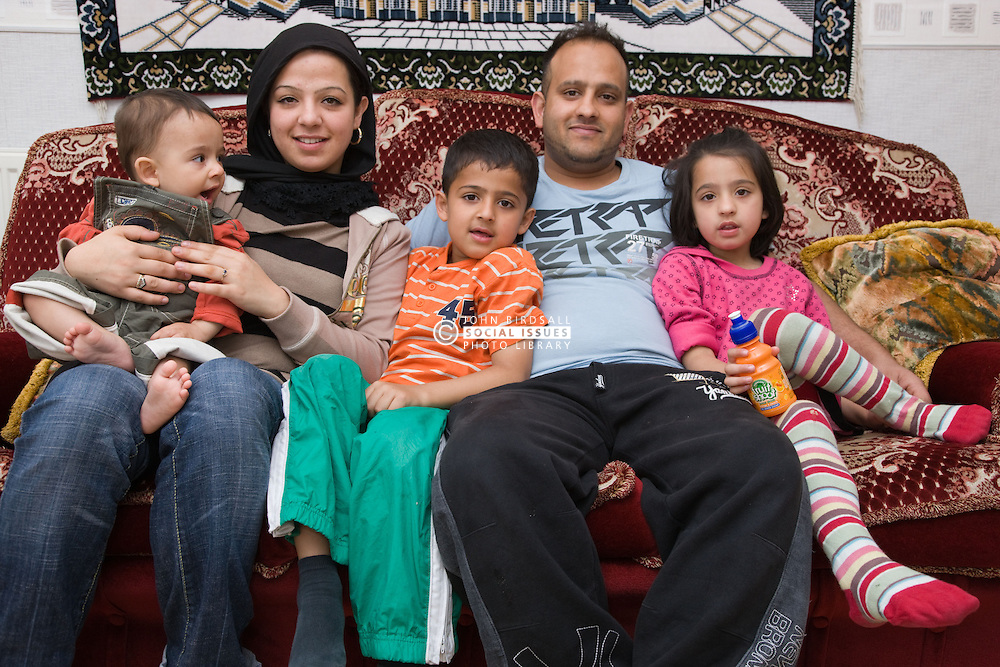 Young family sitting on the sofa at home together,