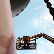 view from below of a shipyard worker spray painting a ship red in Dubai