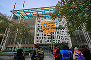"""People walk by and observe a banner hanging on the Home Office building entry that reads """"COP26: Invest in a Plant-based future"""". It is unveiled by Animal Rebellion protestors who have scaled DEFRA in the early morning of Tuesday, Oct 26, 2021, in central London, demanding government support for a plant-based food system ahead of COP26 which is to be held in six days. The protestors have said that they will take action until the government defunds meat and subsidises a plant-based transition. (VX Photo/ Vudi Xhymshiti)"""