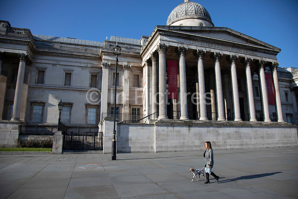 Trafalgar Square and the National Gallery empty and almost deserted apart from a dog walker due to the Covid-19 outbreak social distancing on what would normally be a busy, bustling day with hoards of people out to shop and socialise on 22nd March 2020 in London, England, United Kingdom. Coronavirus or Covid-19 is a new respiratory illness that has not previously been seen in humans. While much or Europe has been placed into lockdown, the UK government has announced more stringent rules as part of their long term strategy, and in particular social distancing.