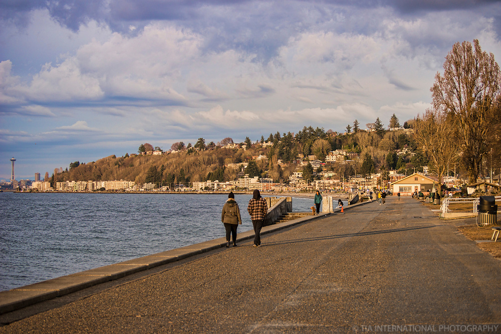 The promenade at Alki Beach Park is typically filled with pedestrians strolling up and down along the Puget Sound. Even with warmer temperatures with the arrival of Spring, many people remain indoors. (March 22, 2020).