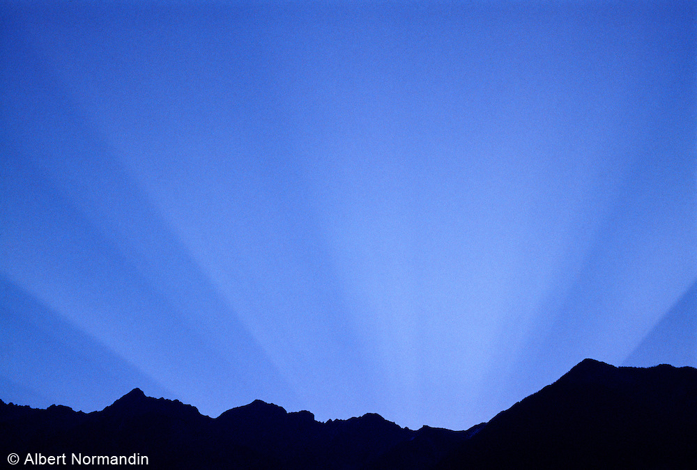 Sunrise rays in sky over Rocky Mountains