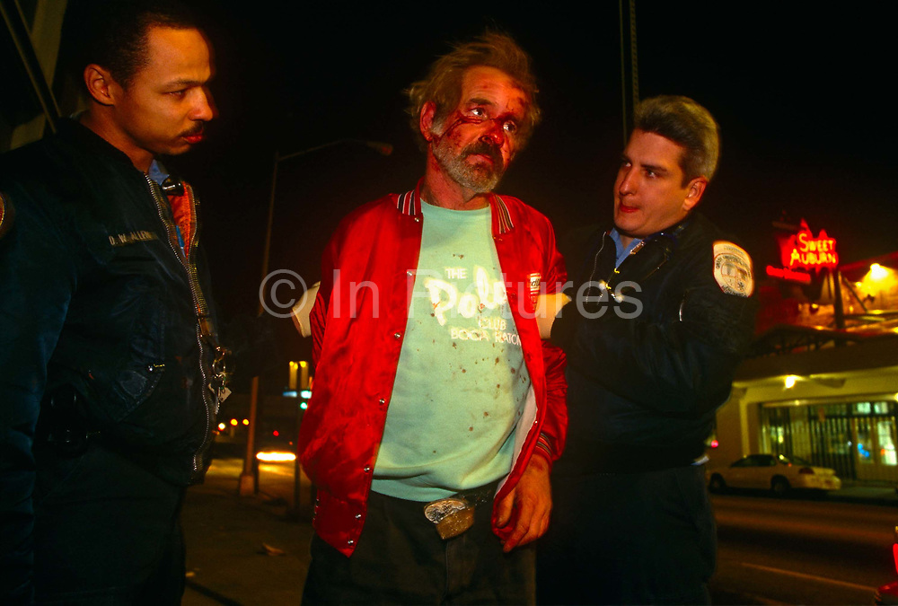 Paramedics assist a bloodied man under the influence of alcohol, picked up by Atlanta police after a street altercation. Standing between the medical staff that have been called to assist him and determine whether he needs treatment, the man looks dazed and confused, unsure where he is and what has happened to him. He wears a red sports jacket and the blood from a facial would have dripped and spattered his shirt underneath. The streets of Atlanta are dark in this neighbourhood, used to violence among the homeless and those dependent on alcohol.