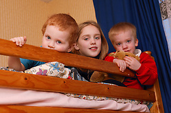 Young children sitting on their bunk beds,