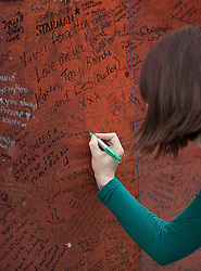 © Licensed to London News Pictures. 10/01/2017. London, UK. A fan writes a message next to a mural and shrine to David Bowie in Brixton. David Bowie who died a year ago today, was born in Brixton, south London. Photo credit: Peter Macdiarmid/LNP