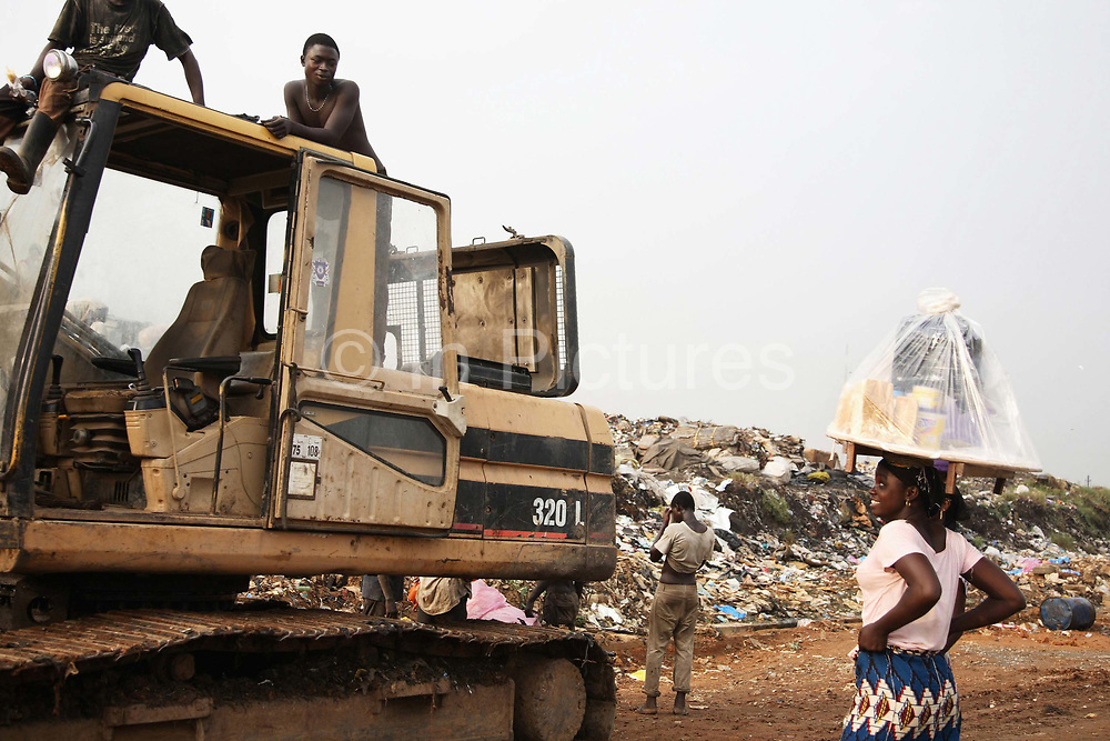 A girl selling drinks on the site chats to boys working on the rubbish dump. Olusosum dump site, Lagos.  Goverment run by the agency Lagos Waste Management Authority ( LAWMA ). One of 6 sites taking in general waste from all over Lagos.  E-waste is not allowed on site, but some does appear from the gerneral waste  collected all over Lagos.  Scavengers,- people, are making a living out of shifting through the rubbish and selling their collections for recycling.Some of the scavengers live on site, too poor to pay for accommodation any where else. This picture is part of an undercover investigation by Greenpeace and Sky News.  A TV-set originally delivered to a municipality-run collecting point in UK for discarded electronic products was tracked and monitored by Greenpeace using a combination of GPS, GSM, and an onboard radiofrequency transmitter placed inside the TV-set.  The TV arrived in Lagos in container no 4629416 and was found in Alaba International Market and bought back by Greenpeace activist. The TV was subsequently brought back to England and used as proof of illegal export of electronic waste. A number of individual are currently on trial in London in connection with illegal exports(Nov 2011)