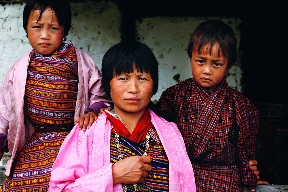 A woman and her children dressed in traditional Bhutanese clothes, (Woman and girl in a kira, and boy at right in a gho) which have been mandated by the country's king to be worn by all adult citizens. Shingkhey Village, Bhutan. From Peter Menzel's Material World Project.