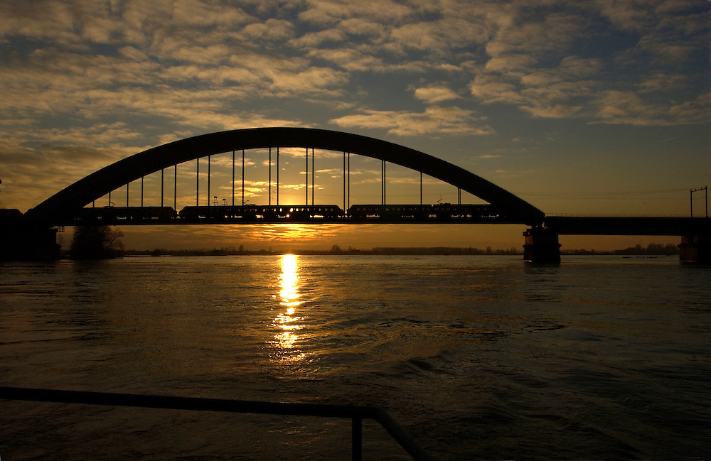 Nederland, Culemborg, 10 jan 2003..Brug over de Lek bij Culemborg met ondergaande zon en trein...Foto (c) Michiel Wijnbergh/Hollandse Hoogte
