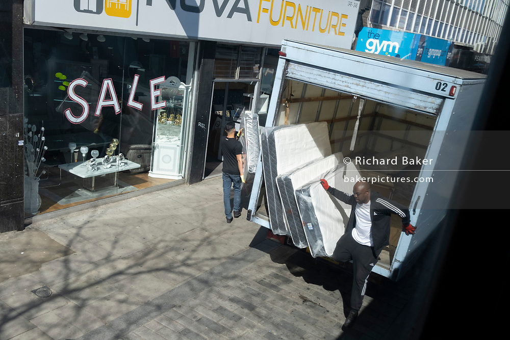 A delivery of matresses destined for a local furniture retailer is offloaded from the back of a box van on the Walworth Road, on 23rd April 2021, in London, England.