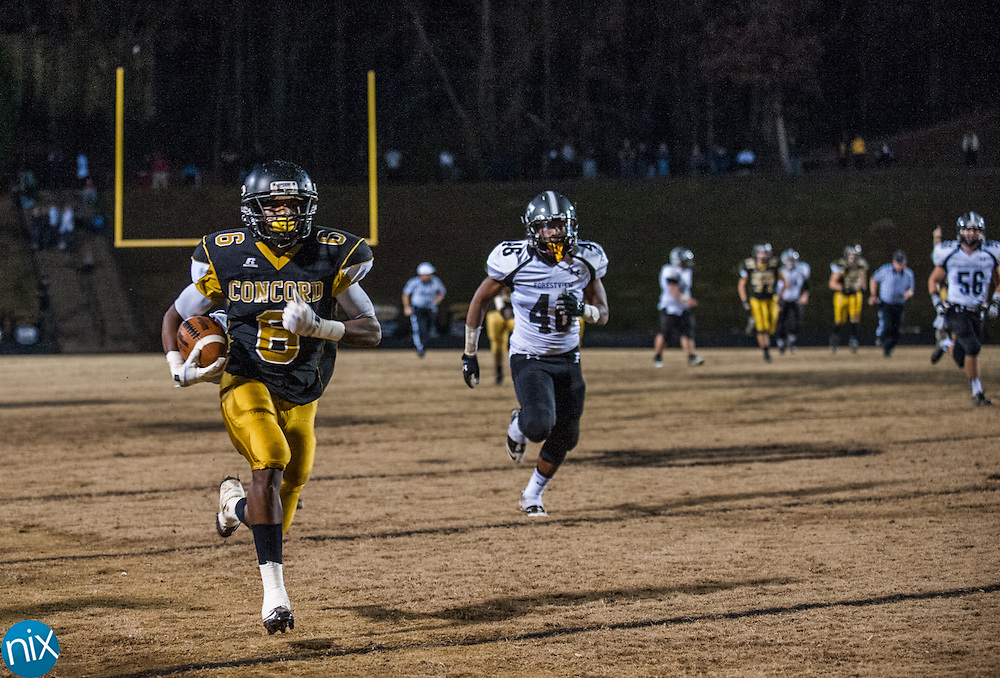 Concord's Myles Neils (6) gets ahead of Forestview defenders on his way to score during the semi finals of the NCHSAA 3A playoffs Friday night at Concord High School. The Spiders defeated Forestview 35-14 to secure a spot in the state championship game.