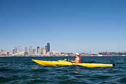 USA, Washington, Seattle. Woman kayaking in Elliott Bay near downtown Seattle. MR