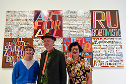 "© Licensed to London News Pictures. 04/09/2018. LONDON, UK.  Celebrated artist Bob and Roberta Smith RA (C), poses with his daughter Etta Voorsanger (L) and wife Etta Voorsanger (R) at the unveiling  of his new work ""The Secret of a Good Life"", the first display by a Royal Academician in the new Ronald and Rita McAulay Gallery, a new space dedicated to site-specific installations by Royal Academicians in the new Royal Academy in Piccadilly.  This and other works are on display 4 September to 3 February 2019.  Photo credit: Stephen Chung/LNP"