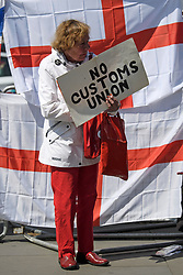 """© Licensed to London News Pictures. 15/05/2019. London, UK. A Brexit supporter holding a sign reading """"NO CUSTOMS UNION"""" is seen stood in front of the Flag of St George in Westminster, London. Government has announced that MPs will get another chance to vote on Theresa May's Brexit Bill in early June, after EU parliament elections. Photo credit: Ben Cawthra/LNP"""