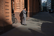 A businessman on a cigarette break smokes outside offices in late summer sunshine on 8th September 2016, in the City of London, England UK. The young man seemingly works in the heart of the capitals financial district, founded by the Romans in the first century.