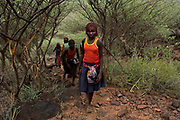 Pokot girls walk towards their homes prior to the beginning of their circumcision ceremony, about 80 kilometres from the town of Marigat in Baringo County, Kenya, October 16, 2014. The ceremony starts the evening before the girls get circumcised and involves women and elders of the community gathering together, singing and dancing through out the night in encouragement to the girls who together wait inside a hut for first light. The traditional practice of circumcision within the Pokot is a right of passage that marks the transition to womanhood and a requirement to marriage within the community.