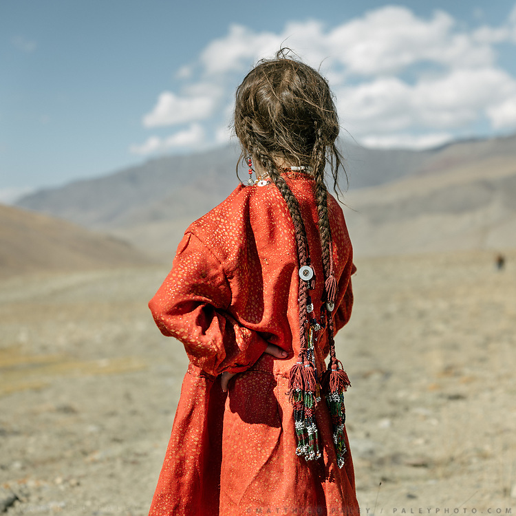"""Detail of the dress and hair style of a young wakhi girl named Mistera. Women and girls washing clothes near camp. Life in Baiqara, a Wakhi High pasture inhabited for about 6 months of the year, from May until October. Guiding and photographing Paul Salopek while trekking with 2 donkeys across the """"Roof of the World"""", through the Afghan Pamir and Hindukush mountains, into Pakistan and the Karakoram mountains of the Greater Western Himalaya."""