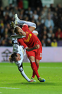 Swansea city's Michu  © gets tangled up with Liverpool's Martin Skrtel after going for a header. Barclays Premier league match, Swansea city v Liverpool at the Liberty Stadium in Swansea, South Wales on Monday 16th Sept 2013. pic by Andrew Orchard, Andrew Orchard sports photography,