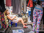 30 MAY 2013 - BANGKOK, THAILAND:  A vendor dozes in her shop in Bobae Market in Bangkok. Bobae Market is a 30 year old famous for fashion wholesale and is now very popular with exporters from around the world. Bobae Tower is next to the market and  advertises itself as having 1,300 stalls under one roof and claims to be the largest garment wholesale center in Thailand.    PHOTO BY JACK KURTZ