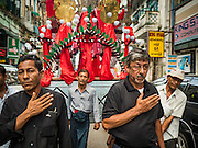 23 OCTOBER 2015 - YANGON, MYANMAR: An Ashura procession goes past Punja Mosque in Yangon. Ashura commemorates the death of Hussein ibn Ali, the grandson of the Prophet Muhammed, in the 7th century. Hussein ibn Ali is considered by Shia Muslims to be the third imam and the rightful successor of Muhammed. He was killed at the Battle of Karbala in 610 CE on the 10th day of Muharram, the first month of the Islamic calendar. According to Myanmar government statistics, only about 4% of the population is Muslim. Many Muslims have fled Myanmar in recent years because of violence directed against Burmese Muslims by Buddhist nationalists.    PHOTO BY JACK KURTZ